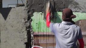 Albañil de sexo masculino enmascarado de la construcción que enyesa el cemento en la pared almacen de metraje de vídeo