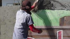 Albañil de sexo masculino enmascarado de la construcción que enyesa el cemento en la pared metrajes