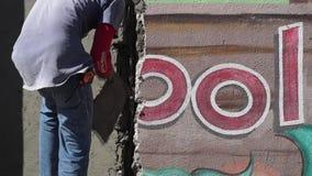 Albañil de sexo masculino enmascarado de la construcción que enyesa el cemento en la pared almacen de video