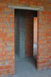 Albañil que construye la nueva casa con las paredes de ladrillo, cuartos interiores Imágenes de archivo libres de regalías