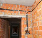 Albañil que construye la nueva casa con las paredes de ladrillo, cuartos interiores, atando con alambre Imágenes de archivo libres de regalías