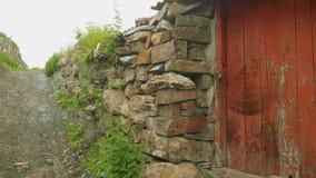 Albañilería y puerta vieja en pequeño pueblo en montañas osetias almacen de video