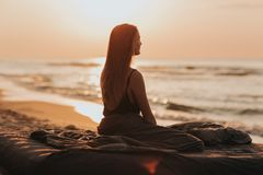 Alba adorabile di mattina in mare, siluetta della ragazza al tramonto la donna si rilassa dal mare Concetto di meditazione fotografia stock
