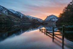 Alba arancio di inverno a Buttermere nel distretto del lago, Regno Unito Fotografie Stock
