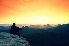 Alba arancio di sorveglianza enjoing dell'uomo in montagne Immagine Stock