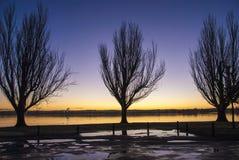 Alba attraverso un lago Fotografie Stock