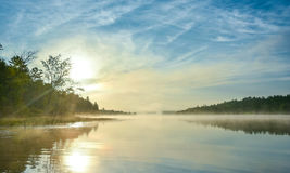 Alba brillante sulla mattina nebbiosa e nebbiosa di estate sul lago corry Fotografie Stock Libere da Diritti