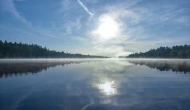 Alba brillante sulla mattina nebbiosa e nebbiosa di estate sul lago corry Fotografie Stock