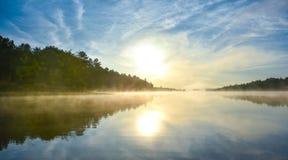 Alba brillante sulla mattina nebbiosa e nebbiosa di estate sul lago corry Fotografia Stock