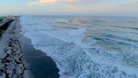 Alba calda di tramonto sopra l'onda spumosa bianca calma della linea della costa della riva della spiaggia del cacao di Florida l video d archivio