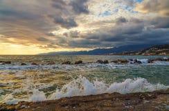 Alba con belle di nuvole e delle le onde colorate multi che avvolgono sulla riva in priorità alta, Creta Grecia Fotografia Stock