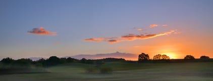 Alba con le nubi ardenti sopra un ampio paesaggio rurale con il mea immagini stock