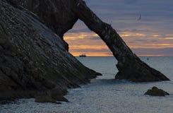 Alba con le nuvole rosse alla roccia delle fiddle dell'arco vicino a Portknockie fotografia stock