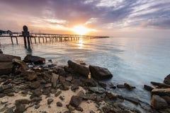 Alba dalla riva con la priorità alta della roccia per fondo Fotografie Stock