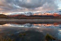 Alba della neve di riflessione delle montagne del lago Immagine Stock