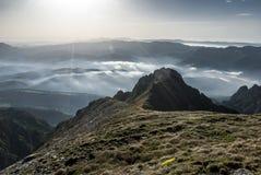 Alba delle creste della montagna sopra le nuvole Fotografia Stock