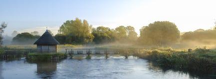 Alba di autunno con foschia sulle trappole della Camera dell'anguilla sulla prova del fiume vicino a Longstock, Hampshire, Regno  immagine stock