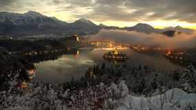 Alba di inverno nel lago Bled con neve sugli alberi Immagini Stock