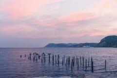 Alba di Mar Nero Nuvole rosa, le montagne ed uccelli che si siedono sui tubi del metallo Fotografia Stock