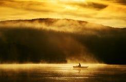 Alba di primo mattino, canottaggio sul lago alla luce solare Immagini Stock