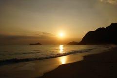 Alba di primo mattino sulla spiaggia di Waimanalo sopra il bursti dell'isola della roccia Immagini Stock Libere da Diritti