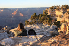 Alba di sorveglianza del viaggiatore con zaino e sacco a pelo sopra il grande canyon Immagine Stock