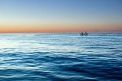Alba di tramonto in mare aperto con il chiaro cielo calmo drammatico Fotografie Stock Libere da Diritti