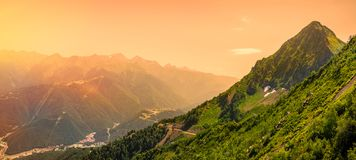 Alba luminosa nelle montagne Vista panoramica della valle con gli edifici residenziali, circondata dalle montagne con le cabine d immagini stock