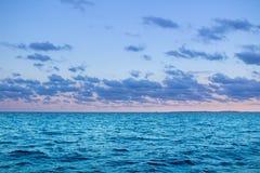 Alba in mare aperto con il chiaro cielo calmo nuvoloso drammatico Immagine Stock