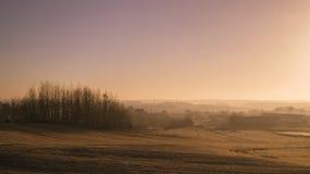 Alba naturale di tramonto sopra il campo o il prato Cielo drammatico luminoso e terra scura Sun sopra orizzonte, orizzonte caldo Immagine Stock