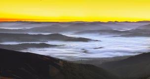 Alba nebbiosa nelle montagne Fotografia Stock