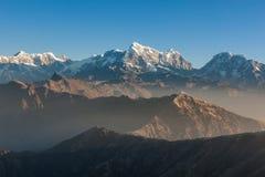 Alba nebbiosa sopra il paesaggio nevoso delle montagne con Immagine Stock