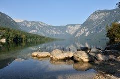 Alba nel lago Bohinj con le pietre. Immagini Stock