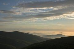 Alba nelle montagne con nebbia nella valle Immagini Stock
