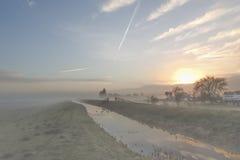 Alba in Olanda su una mattina nebbiosa di inverno con la brina sull'erba verde immagine stock