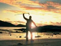 Alba soleggiata della molla dell'orologio del camminatore sopra il mare Viandante con il supporto dello zaino sulla riva sabbiosa Fotografia Stock Libera da Diritti