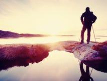 Alba soleggiata di viaggiatore con zaino e sacco a pelo della radura alta dell'orologio sopra il mare La viandante della viandant Fotografia Stock