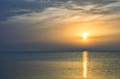 Alba soleggiata in mare, barca sulle onde Immagine Stock