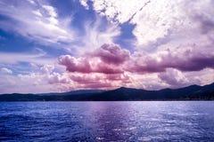 Alba sopra il mare con le nuvole porpora immagine stock