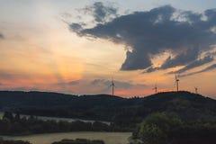 Alba sopra la foresta verde ed i mulini a vento moderni fotografie stock libere da diritti