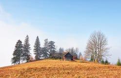 Alba sopra la valle nebbiosa dell'alta montagna con le vecchie case di legno su una collina in una foresta della montagna Fotografie Stock Libere da Diritti