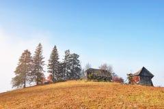 Alba sopra la valle nebbiosa dell'alta montagna con le vecchie case di legno su una collina in una foresta della montagna Immagini Stock
