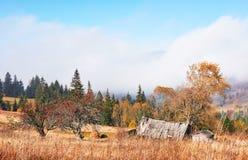 Alba sopra la valle nebbiosa dell'alta montagna con le vecchie case di legno su una collina in una foresta della montagna Immagini Stock Libere da Diritti
