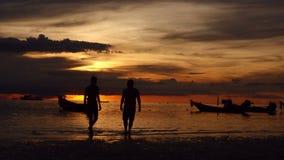 Alba su una spiaggia tropicale siluette delle barche e la gente, sabbia e mare archivi video