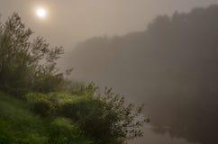 Alba sul fiume in una nebbia Fotografia Stock