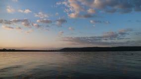 Alba sul lago, sulla pesca iniziale o sul canottaggio Fotografia Stock