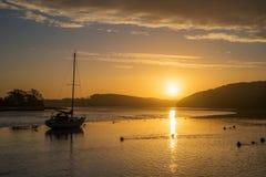 Alba sul lynher del fiume con il bello cielo e riflessioni dorate ai tedeschi della st, Cornovaglia, Regno Unito Fotografia Stock