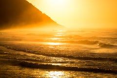 Alba sulla spiaggia con la costa della montagna fotografia stock libera da diritti