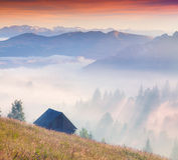Alba variopinta di estate in montagne nebbiose Immagini Stock