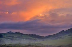 Alba vibrante drammatica sopra Misty Hills su una mattina di estate, montagne di Altai, il Kazakistan Fantasyland, nuovo giorno,  fotografia stock